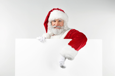 Portrait of Santa Claus with blank poster on white background