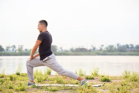 Sporty young man training outdoors near river Standard-Bild