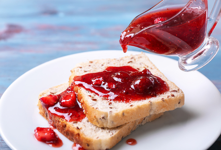 Pouring of delicious strawberry jam onto slices of bread, closeup