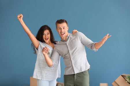 Happy young couple with key from their new house on color background