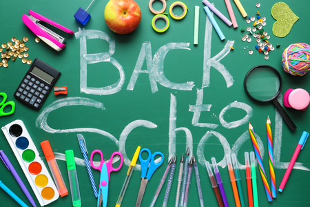 Set of stationery and words BACK TO SCHOOL on chalkboard