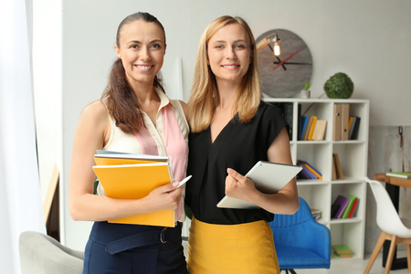 Young businesswomen with tablet PC and documents in office