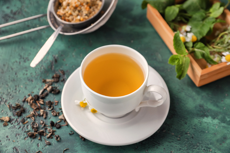 Cup of delicious camomile tea on green table