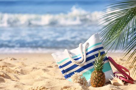 Set of beach items with pineapple on sand near sea