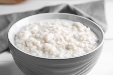 Delicious rice pudding in bowl on table, closeup