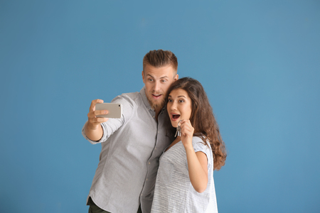 Happy young couple taking selfie with key from their new house on color background Imagens