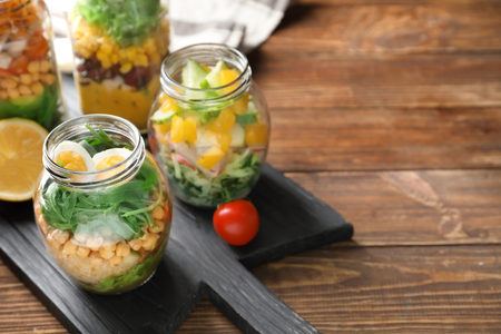 Delicious vegetable salads with egg in mason jars on wooden board