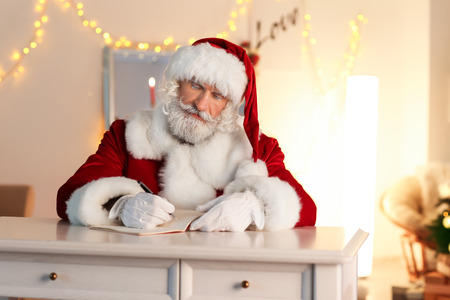Santa Claus writing in notebook while sitting at table in room decorated for Christmas Stock Photo
