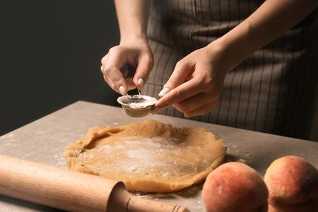Woman preparing dough for peach galette at table