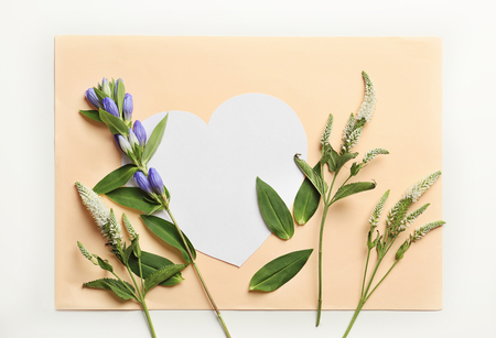 Beautiful flowers with heart-shaped blank card on white background