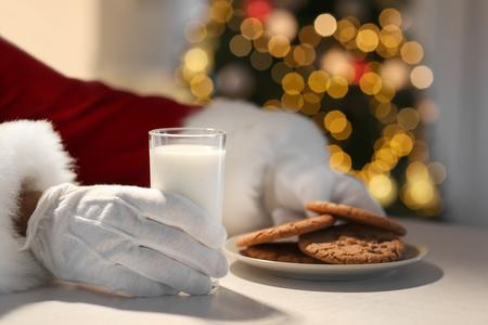 Santa Claus eating cookies and drinking milk at table, closeup Stock Photo