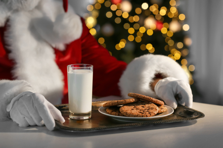 Santa Claus eating cookies and drinking milk at table, closeup Standard-Bild