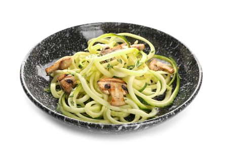 Plate with zucchini spaghetti and mushrooms isolated on white