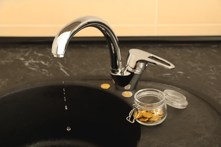 Jar with coins near metal tap. Water saving concept