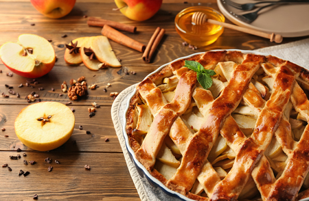 Dish with delicious apple pie on wooden table