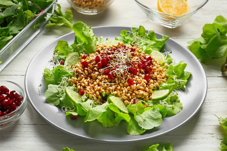 Plate with healthy fresh salad on white wooden table Stok Fotoğraf
