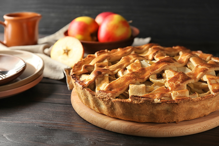 Board with delicious apple pie on wooden table