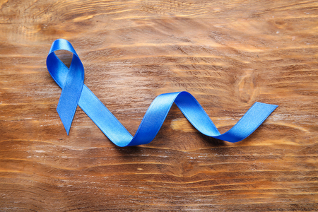 Blue ribbon on wooden background. Cancer concept