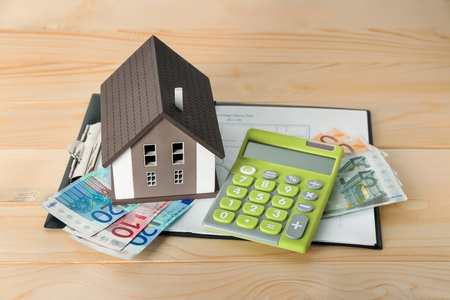 House model, calculator and banknotes on wooden table. Mortgage concept Stock Photo