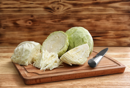 Wooden board with cut cabbage on table Reklamní fotografie