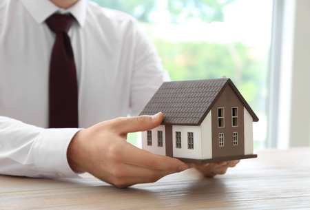 Real estate agent with house model at wooden table. Mortgage concept Stock Photo