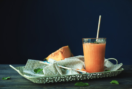 Glass with delicious melon smoothie on wooden table