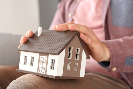 Man holding house model, closeup. Mortgage concept Stock fotó