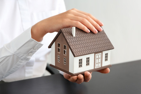Real estate agent with house model at dark table, closeup