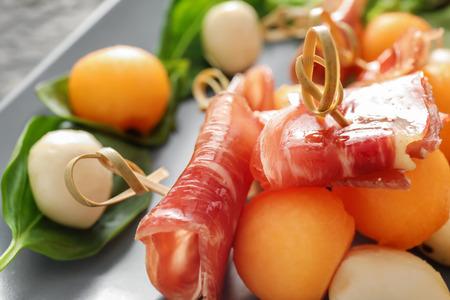 Delicious melon balls with prosciutto and mozzarella cheese on plate, closeup