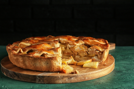 Board with delicious apple pie on green table