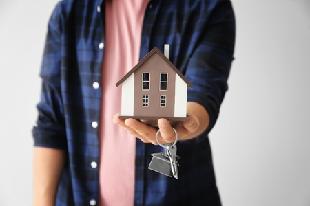 Man holding house model and key on light background, closeup. Mortgage concept
