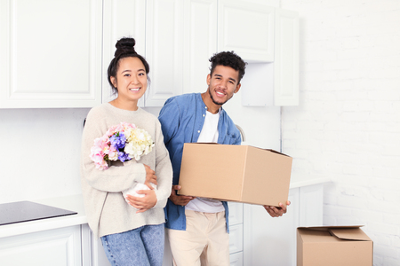 Happy interracial couple unpacking box in kitchen. Moving into new house 版權商用圖片