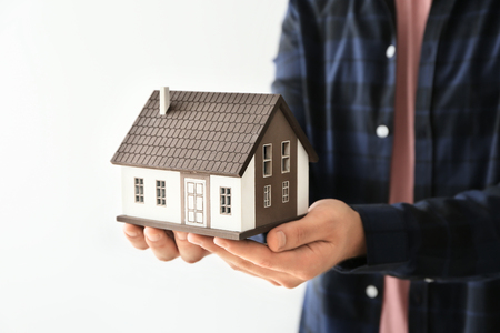 Man holding house model on light background, closeup. Mortgage concept