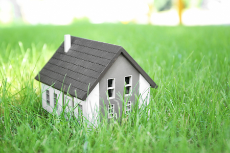 House model on green lawn. Mortgage concept