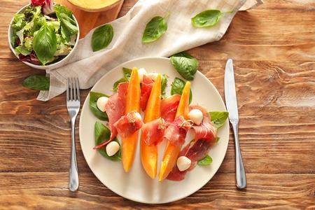 Delicious melon with prosciutto and mozzarella cheese on wooden table 写真素材