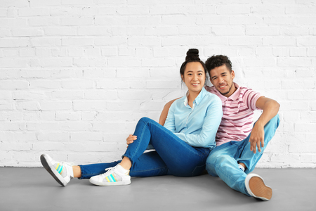 Happy interracial couple sitting on floor in empty room. Moving into new house Imagens