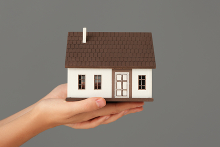Woman holding house model on grey background. Mortgage concept
