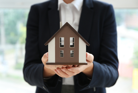 Real estate agent with house model indoors
