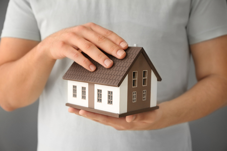 Man holding house model, closeup. Mortgage concept