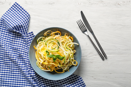 Spaghetti with zucchini in bowl on light wooden table 免版税图像