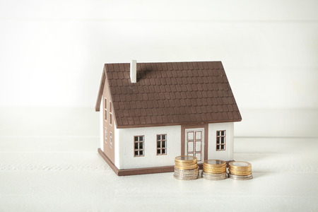 House model and coins on white table. Mortgage concept