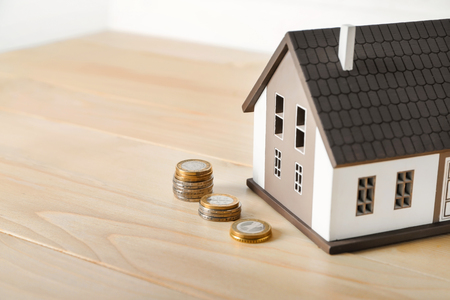 House model and coins on wooden table. Mortgage concept