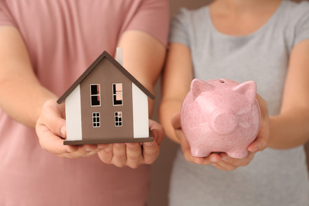 Young couple holding house model and piggy bank, closeup. Mortgage concept