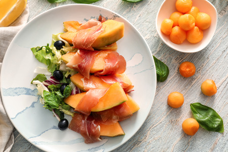 Delicious melon wrapped in prosciutto on plate 写真素材