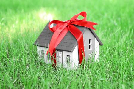 House model with ribbon on green lawn. Mortgage concept