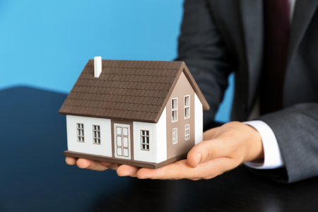Real estate agent with house model at dark table. Mortgage concept