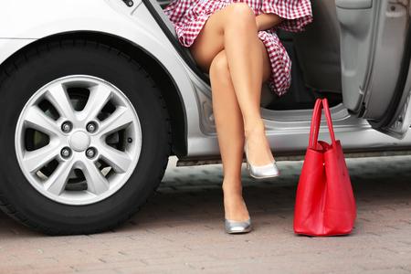 Mujer joven con piernas delgadas en tacones saliendo del coche