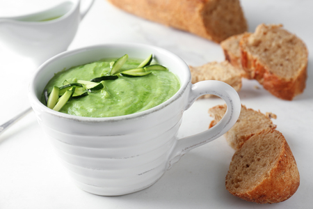 Tasty zucchini soup in cup with bread on light table