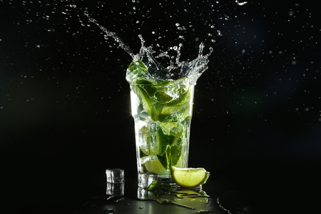 Glass of fresh mojito with splashes on dark background