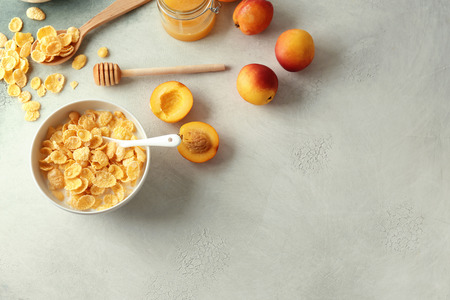 Bowl with healthy cornflakes, milk, honey and peaches on light table